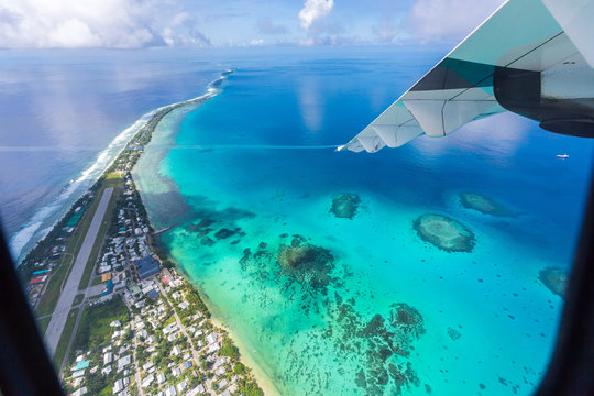 Tuvalu lagoon under wing of an airplane. Aerial view of Funafuti atoll and the airstrip of International airport in Vaiaku. Fongafale motu. Island nation in Polynesia, South Pacific Ocean, Oceania.