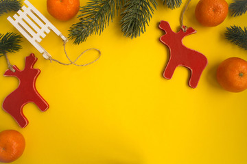 Christmas composition with wooden toys and  tangerines  on the yellow background.Top view.Copy space.
