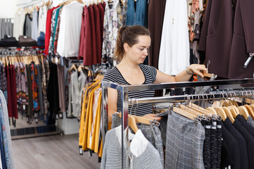 Woman choosing new clothes in showroom