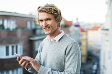Young man with smartphone standing on a balcony in city, texting.
