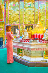 The young Burmese parishioner pray in Su Taung Pyae Pagoda, Mandalay, Myanmar