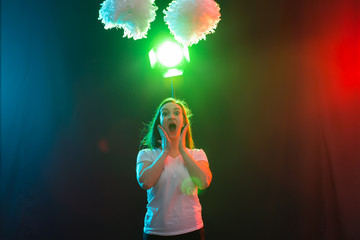 Dance, sport and people concept - pretty young woman dancing in darkness with pompoms and smiling