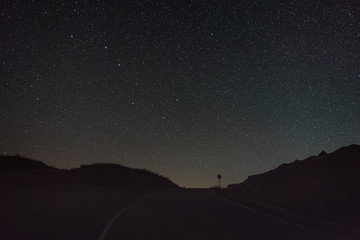 The stars of the constellation Ursa Major in a clear night sky above the road.