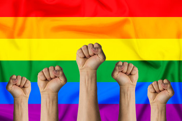 Hands raised up and clenched in a fist against the background of the LGBT flag. Concept of unity of the LGBT community and the protection of the rights of sexual minorities