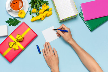 Flat lay top view womens hands write congratulations on empty sheet, red present box with gold ribbon, cup of tea, notebook, yellow chrysanthemums on blue background. Holiday concept, Congratulations