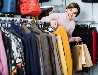 Female shopper examining warm sweaters in women's cloths shop
