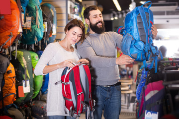young couple examining rucksacks in sports equipment store
