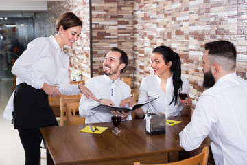 Smiling woman waitress taking order from visitors