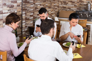 group of concentrated friends busy with phone in restaurant