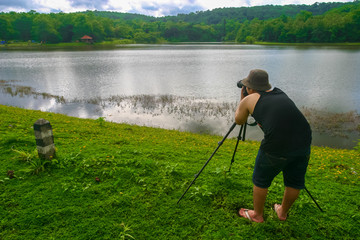 My self Photography before raining. Alone man wearing black cloth using camera and tripod taking landscape image with hills and lagoon in green forest. Background for photos training or weekend travel