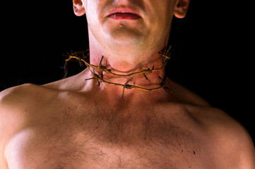 barbed wire, on the neck.  emotional portrait on a black background. neck in blood
