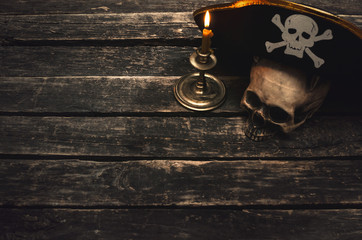 Pirate captain table with pirate hat, human skull and burning candle. Treasure hunter concept background.
