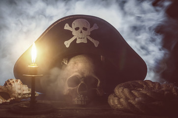 Human skull with pirate captain hat above, burning candle, seashell and mooring rope on the wooden table in the mystic smoke.