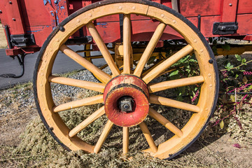 Old Wooden Wagon Wheel On Red Wagon