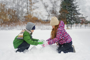 Children playing with a snowman on a winter walk in the park.