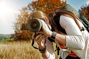 Fotografin mit Kamera in der Abendsonne in der Natur