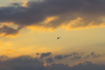 Sunset on the background of turquoise sky - golden rays of the sun, dark clouds and flying helicopter