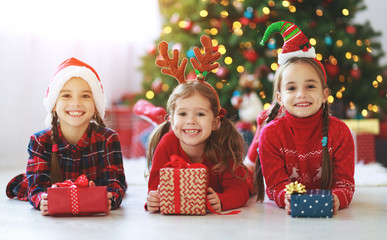 happy children girls with christmas gifts near tree in  morning