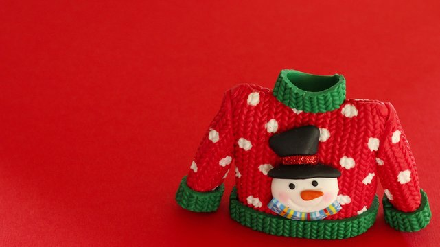red sweater with green collar and sleeve cuffs white snowflakes and snowman with black hat and carrot nose isolated on a festive red background
