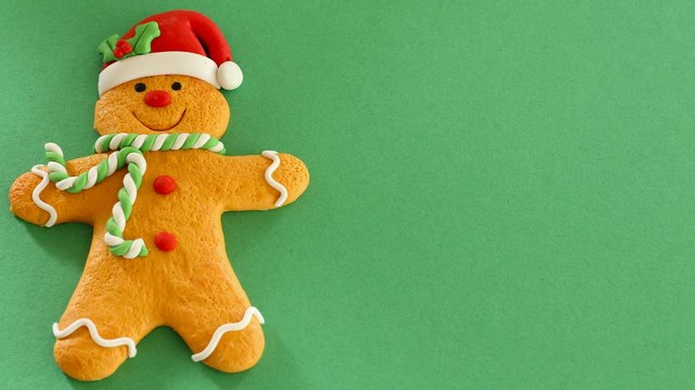 gingerbread man with red hat and buttons green and white scarf isolated on a green background with writing space