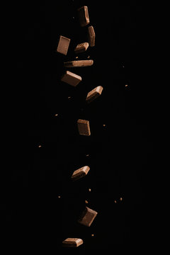 Chocolate pieces and tiles are falling on a black background. Food for food. Candy and chocolate in motion.isolate