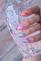 nail art manicure with colorful polish nails and bottle of water. Beauty hand and stylish nails.