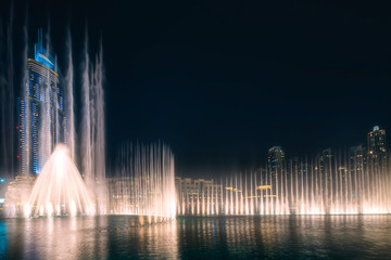 The night cityscape with dancing fountain of Dubai