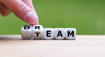 "Hand is turning a dice and changes the word ""dream"" to ""team"""