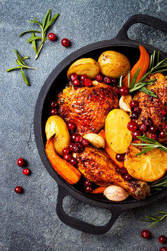 Roasted chicken legs with root vegetables, lemon, garlic, cranberry and rosemary on pan, on black slate stone background