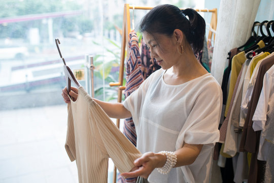 one senior asian woman buying cloth in the shop