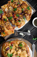 Delicious and appetizing pizza from yeast dough. Delicious and healthy vegetable pizza. Vegetable pizza on a black wooden table.