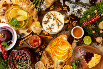 Top view tea assortment with various teapots decorated with cakes, herbs, berries, jam, honey and citrus at wooden table background.