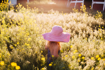 Toddler girl in an oversized pink striped sun hat playing in yellow wildflowers.