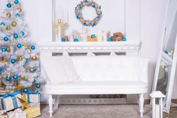 family holiday concept. Merry Christmas and Happy Holidays. Studio with Christmas decor. Winter home decor. Christmas tree, fireplace with firewood Boxes with gifts and golden and blue bows. Xmas