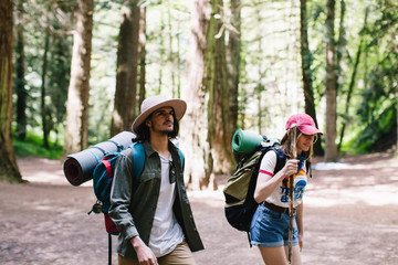 Young hiker couple out for a walk in a big sequoias forest.