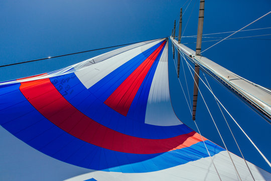 Closeup of a red, blue and white sail on a sailboat