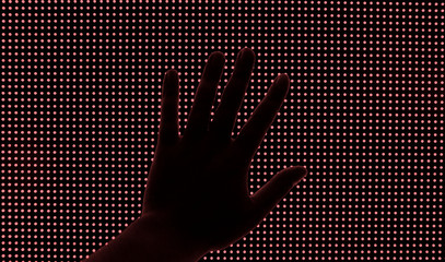 Hand on a big red LED screen.