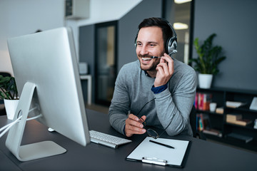 Happy young customer support operator talking to his satisfied client.