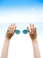 Crop female hands holding sunglasses