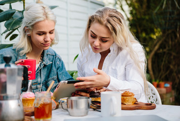 Two women looking at a tablet, working together and having breakfast
