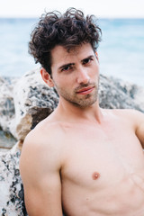 Shirtless man posing on rock