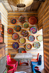 Colorful dishes hung on a wall in an eating area