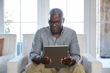 African American Senior man Browsing the internet on a large digital tablet