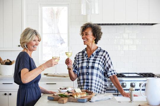 Senior women friends drinking wine in kitchen