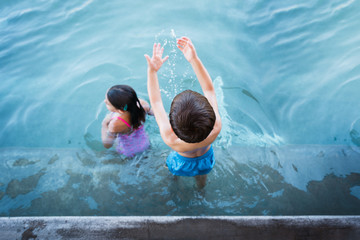Boy Splashing His Sister In The Water