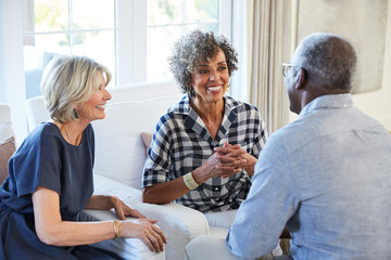 Group of multiethnic senior friends visiting and talking in the living room at home