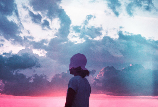 Girl looking out at a cloudy sunset sky
