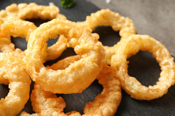 Homemade crunchy fried onion rings on table, closeup