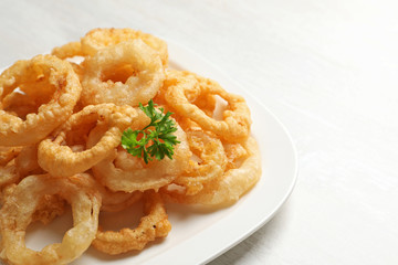 Homemade crunchy fried onion rings in plate on white background, closeup