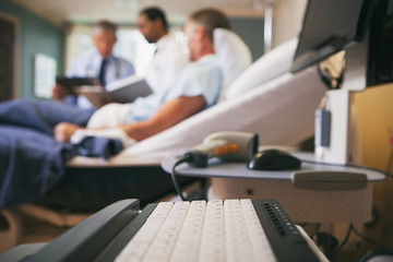 Hospital: Focus On Computer Keyboard WIth Doctors And Patients B
